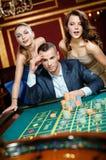 Mann mit zwei Frauen, die Roulette am Kasino spielen Lizenzfreie Stockbilder