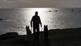 Mann mit zwei Hunden silhouettiert auf den Klippen im Abendlicht in Cornwall Großbritannien Stockbilder