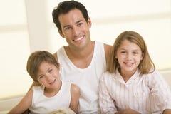 Mann mit zwei jungen Kindern, die beim Bettlächeln sitzen Lizenzfreies Stockbild
