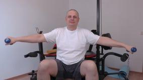 Mann mit zwei kleinen Dummköpfen, die Übung für Schultern tun stock footage