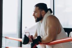Mann nach starkem Training Boxer, der eine Pause trinkt von der Wasserflasche nach der Ausbildung in der Turnhalle macht lizenzfreies stockfoto