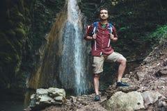 Mann nahe bei einem Wasserfall nach Gebirgstrekking Stockfotografie