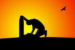 Mann nahe dem Grab am Sonnenuntergang Stockbild
