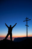Mann nahe dem Kreuz gegen den Himmel am Sonnenuntergang Stockfotografie
