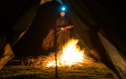 Mann nahe Lagerfeuer nachts Stockfoto