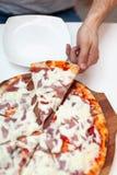 Mann nahm Anschnitt der köstlichen italienischen Pizza In der Rahmenhand, die Scheibe der heißen Pizza mit Schinken auf hölzernem lizenzfreies stockbild