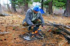 Mann neben Lagerfeuern im Holz stockfotografie