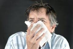 Mann niest in Gewebe-Frontseite Stockfotos