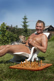 Mann nimmt auf einem grünen Rasen ein Sonnenbad Lizenzfreie Stockfotos