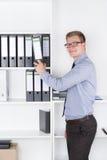 Mann nimmt eine Datei eines Regals im Büro heraus Lizenzfreie Stockfotos