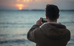 Mann nimmt Fotografiesonnenuntergang über dem Meer Lizenzfreies Stockfoto