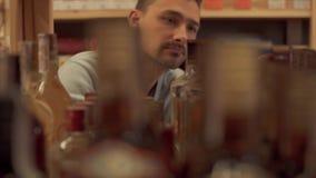 Mann nimmt Ginflasche im Geschäftsabschluß herauf Kunden wählt Getränk im Spirituosenladen stock video
