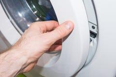 Mann nimmt Kleidung von der Waschmaschine Lizenzfreie Stockbilder