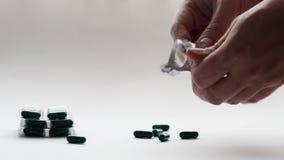 Mann nimmt Pillen aus dem Paket auf einem weißen Hintergrund heraus und möchte Selbstmord, Nahaufnahme festlegen stock footage
