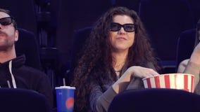 Mann nimmt Popcorn vom Eimer am Kino stock footage