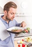 Mann oder Chef, die gegrilltes Steak mit Rosmarin von der Wanne riechen Lizenzfreie Stockfotografie