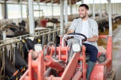 Mann oder Landwirt, die Traktor am Bauernhof fahren Stockfotografie