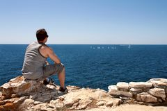 Mann passt die Boote auf, auf das Meer zu segeln Stockfoto