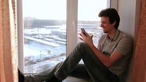 Mann passt etwas im Internet in seinem Handy auf und lacht beim Sitzen auf einem Fensterbrett stock video footage