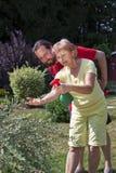 Mann passt Frau an der Gartenarbeit auf Stockfoto