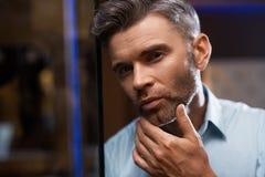 Mann-Pflegen Gut aussehender Mann mit Bart-rührendem Gesicht Zutreffen des transparenten Lacks Stockfotografie