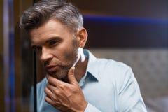 Mann-Pflegen Gut aussehender Mann mit Bart-rührendem Gesicht Zutreffen des transparenten Lacks Lizenzfreie Stockfotografie