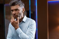 Mann-Pflegen Gut aussehender Mann mit Bart-rührendem Gesicht Zutreffen des transparenten Lacks lizenzfreie stockfotos