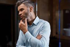 Mann-Pflegen Gut aussehender Mann mit Bart-rührendem Gesicht Zutreffen des transparenten Lacks lizenzfreie stockbilder
