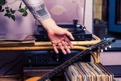 Mann pickingup Gitarre nachdem dem Hören auf Aufzeichnungen Stockfotografie