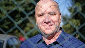 Mann-Porträt-Rückseite des metallischen Zauns von einem Schutz-Bereichs-Lächeln überzeugt stock footage