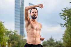 Mann practicing qigong outdoors, office building in background Stock Image