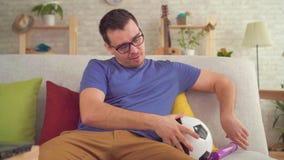 Mann rüttelt einen Fußball mit einer Pumpe, die auf der Couch sitzt stock footage