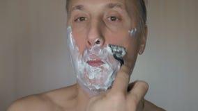 Mann rasiert sein Gesicht Mann, der mit Schaum und manuellem razer sich rasiert stock video footage
