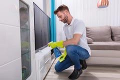 Mann-Reinigungs-Möbel mit Sprühflasche lizenzfreies stockfoto