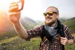 Mann-Reisender mit Bart macht Selfie im Hintergrund von einer Berglandschaft Reise, die Konzept wandert stockbild