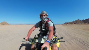 Mann reitet ein Viererkabel-Fahrrad in der Wüste von Ägypten und schießt sich auf einer Aktions-Kamera stock footage