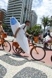 Mann-Reitfahrrad mit Surfbrett Rio Lizenzfreie Stockfotografie