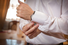 Mann repariert Manschettenknöpfe auf weißem Hemd Lizenzfreie Stockfotografie