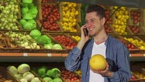 Mann riecht Melone am Supermarkt stock footage