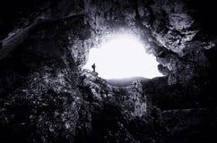 Mann am riesigen Höhleneingang mit steilen Klippen Lizenzfreies Stockbild