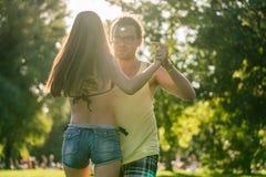 Mann roterande kvinna, medan dansa Bachata i solen Arkivfoton