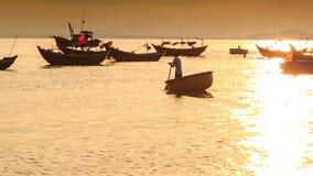 Mann rudert ringsum Fischerboot unter Booten bei Sonnenuntergang in Vietnam stock video footage