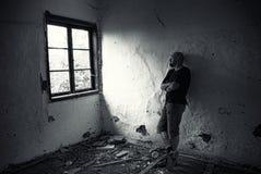Mann in ruiniertem Haus Stockbild