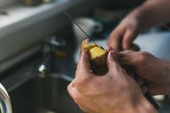Mann säubert Kartoffeln mit einem Messer an der Wanne zu Hause kleine Kartoffeln der Schale Säubern in die Wanne lizenzfreie stockfotos
