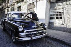 Mann säubert Oldtimer in Havana, Kuba Lizenzfreie Stockfotos