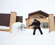 Mann säubert Schnee um das Haus Stockfotos
