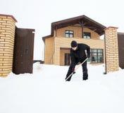 Mann säubert Schnee um Haus Stockfotografie