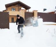 Mann säubert Schnee um Haus Lizenzfreie Stockbilder