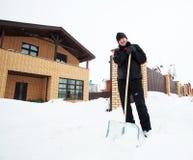 Mann säubert Schneeschaufel nahe dem Haus Stockfotos