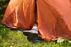 Mann ` s Beine in den schmutzigen touristischen Stiefeln haften heraus in das Zelt Stockfotografie